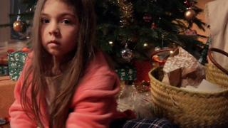 A still from Refuge's new campaign video showing a worried girl next to Christmas presents
