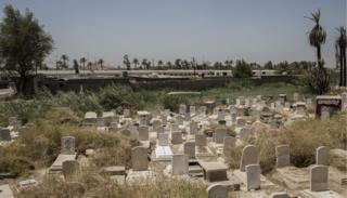 An ancient graveyard split into two to make way for the tracks, with abandoned trains behind