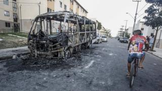 Homem passa de bicicleta ao lado de um micro-ônibus incendiado em Fortaleza, em 4 de janeiro