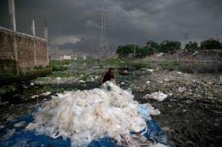 A man washes plastic bags next to a canal