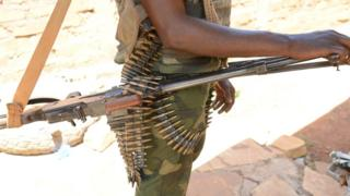 A member of Seleka fighters poses with his weapons on May 15, 2015 near Bambari