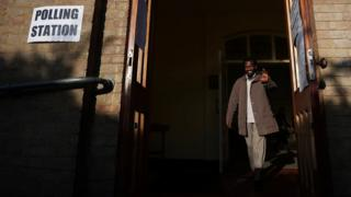 A man waves as he leaves a polling station as voting begins in local government elections in London, Britain