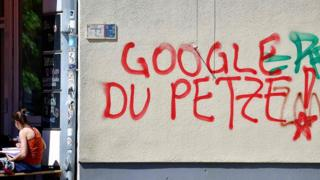 A woman sits next to anti-Google graffiti in Kreuzberg