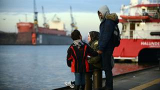 Syrian refugees Wael Al-Awis, 31, right, his wife Reem Haskour, 30, and their son Ali Al-Awis, 6, visit the harbor October 10, 2015 in Hamburg, Germany.