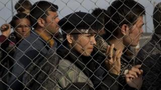 Afghans wait to board a bus on the Greek border after Macedonia refuses to let them enter