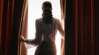 Woman looking through curtains