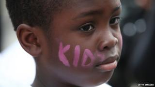 A child with Kids Company written on his cheeks