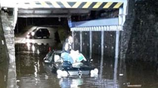 A man stranded on the roof of his car after getting stuck in flood water in Swansea