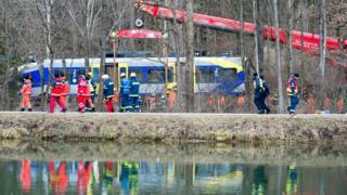 Task force units watch a crane lift a train car at the site of the train accident in Bad Aibling, Germany (11 February 2016)