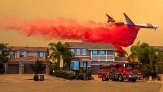 A plane drops retardant over a home