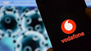 A mobile phone is seen with the Vodafone logo on it in front of an illustration of the coronavirus