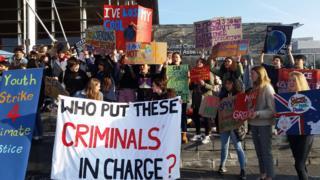Schoolchildren holding up anti-climate change placards