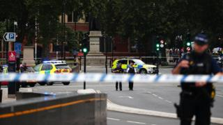 Armed police stand in the street after a car crashed outside the Houses of Parliament in Westminster, London