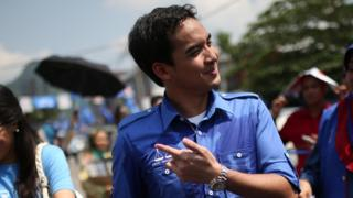 Norashman (C), the son of Malaysia's Prime Minister Najib Razak of ruling party National Front, walks with his sister Nurul Najwa (L) as his father campaigns ahead of the 13th general election in Kuala Lumpur on 22 April 2013.