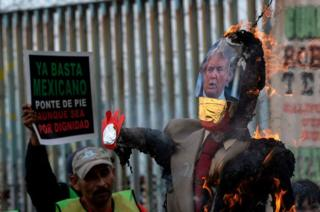 A Trump effigy is burned on the southern side of the US-Mexico border