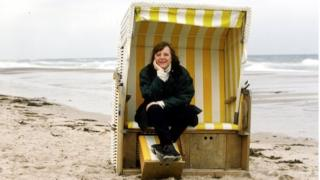Angela Merkel sits a covered seat on the beach