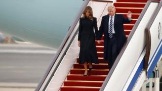 Donald Trump and first lady Melania walk down the stairs on Air Force One