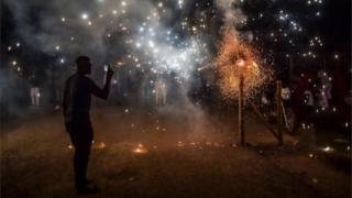 """A man records fireworks with his mobile phone during the """"Adoraciones al Nino Dios"""" celebrations in Quinamayo, department of Valle del Cauca, Colombia, on February 18, 2018."""
