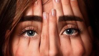 Una imagen de un rostro de mujer con las manos superpuestas