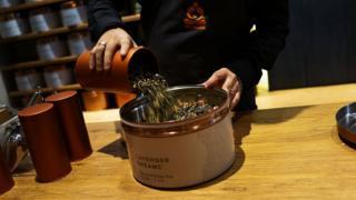 Seorang pegawai menuangkan daun teh di 'bar teh' Teavana yang baru dibuka pada tanggal 24 Oktober, 2013 di New York.