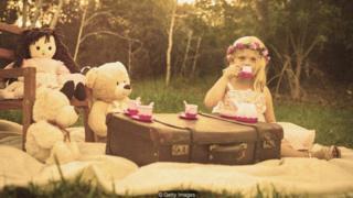 Menina tomando chá com boneca e bichos de pelúcia