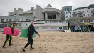 Surfers walking past the entrance to Tate St Ives