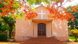Igreja de Araguainha, pequena e pintada de cor de rosa, à frente de uma árvore florida com flores vermelhas
