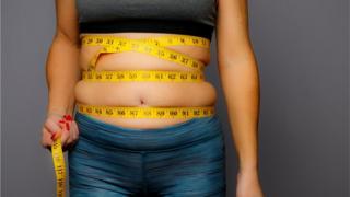Mulher medindo barriga