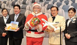 Japan Airlines President Yoshiharu Ueki (2nd L) and Masao Watanabe (2nd R), President of KFC Japan pose with a statue of Colonel Sanders (C) wearing a Santa Claus costume at a press conference to announce plans to offer in flight KFC for 3 months from December 2012