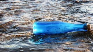 Una botella azul flotando en el agua