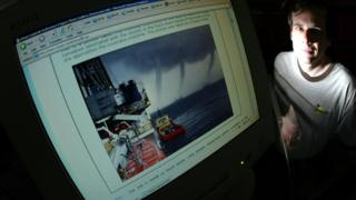 David Mikkelson by his computer monitor with a doctored photo in 2004