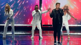 The UK entry to Eurovision 2019 Michael Rice sings on stage with back up dancers