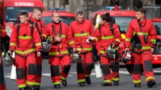 Firefighters walk near Paris police headquarters.
