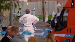 Police tape and forensic staff