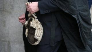 A barrister holds his wig as he arrives at The Old Bailey