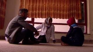 Menino afegão (à dir) de nove anos conversa com equipe da BBC