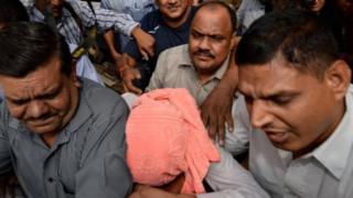 Indian policemen escort the juvenile (C, in pink hood), accused in the December 2012 gang-rape