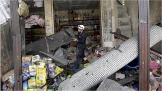 A civil defence member looks for survivors in a damaged shop in the village of Hesh in Idlib province
