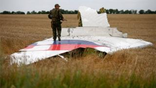 An armed pro-Russian separatist stands on part of the wreckage of the Malaysia Airlines Boeing 777 plane after it crashed near the settlement of Grabovo in the Donetsk region, July 17, 2014