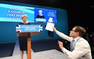 A man holds a piece of paper with P45 written on it as Britain's Prime Minister Theresa May (L) delivers her speech on the final day of Conservative Party Conference in Manchester, Britain, 04 October 2017. The P45 is a reference code for a form on 'Details of employee leaving work' and usually associated with a termination of employment. The conference ran from 01 to 04 of October 2017