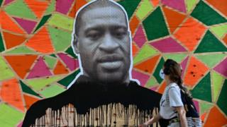A woman walks past a boarded up store front with a George Floyd mural