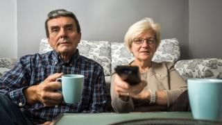 Couple watching TV at their home