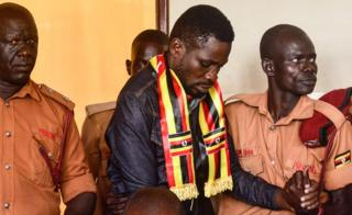 Bobi Wine surrounded by prison guards, one holding his hand, in court in Gulu, northern Uganda - Thursday 23 August 2018
