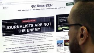A man views the front-page of the online edition of the Boston Globe. Photo: 16 August 2018