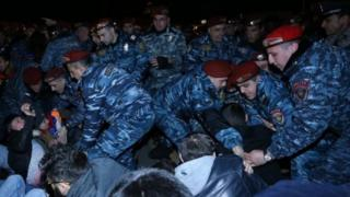 polis Yerevanda küçənin ortasında oturub yolu bağlayan nümayişçiləri kənara çıxardır