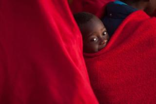A child smiles from behind a red blanket.