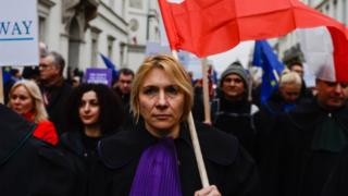A judge holds a Polish flag during a march against judicial reforms in Warsaw on 11 January 2020.