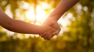 Generic image of a woman holding a child's hand
