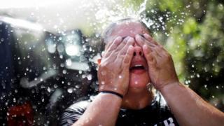 Una mujer en Puerto Rico se refresca luego de llenar recipientes con agua debido a la escasez de este recurso tras el huracán María