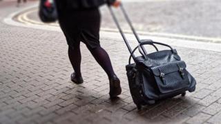 Mulher puxando mala de rodinha